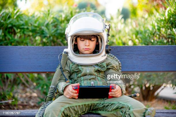 boy wearing a space suit and sitting on a bench, playing alone with video games - space helmet stock pictures, royalty-free photos & images