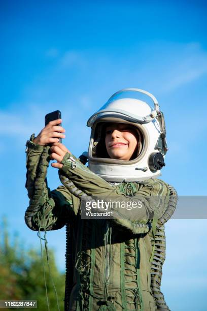 boy wearing a space suit and taking a selfie - space suit stock pictures, royalty-free photos & images