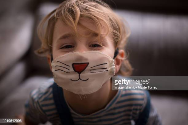 boy wearing a surgical mask painted as a cat - disfraz fotografías e imágenes de stock