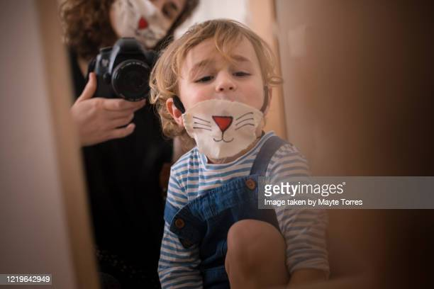 boy wearing a surgical mask painted as a cat while mom takes a photo through the mirror wearing the same mask - funny surgical mask stock pictures, royalty-free photos & images