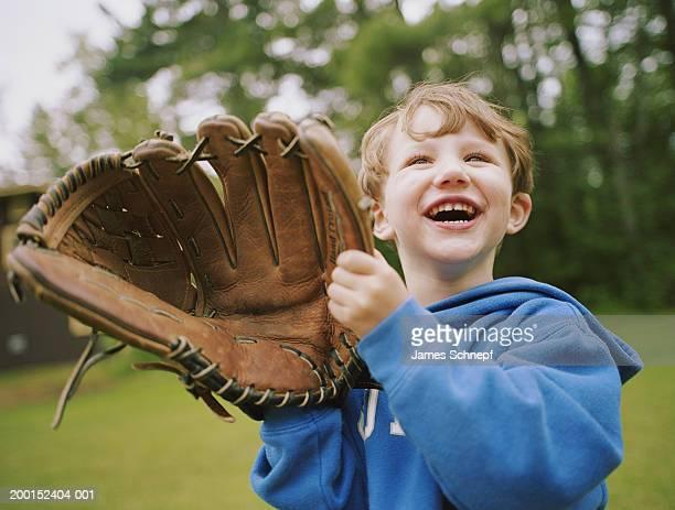 Boy (2-4) wearing adult baseball glove, smiling