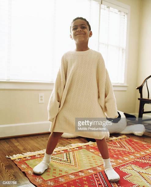 Boy (5-7) wearing adult sweater, smiling, portrait