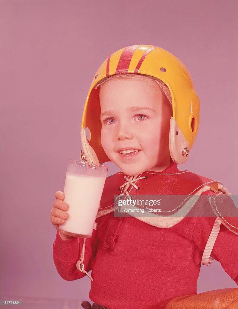 Boy wearing American football kit, holding glass of milk. (Photo by H. Armstrong Roberts/Retrofile/Getty Images) : Stock Photo