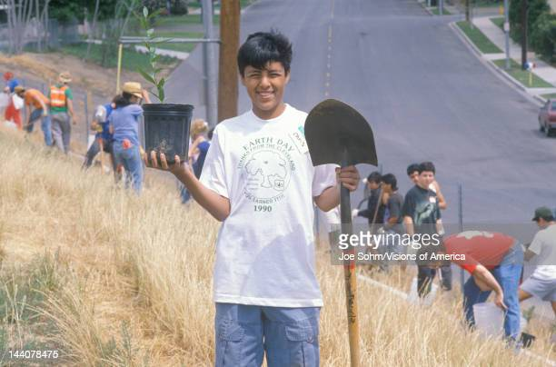 Boy wearing an Earth Day t-shirt participating in a tree planting by the Clean & Green volunteers of the Los Angeles Conservation Corps