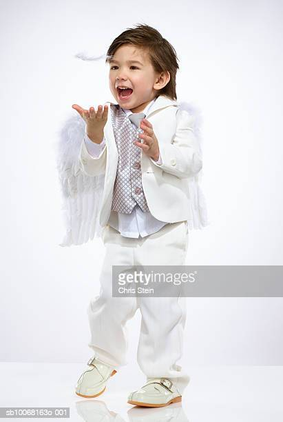 Boy (2-3) wearing angel costume, catching feather, studio shot