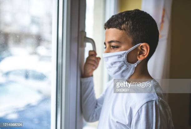 boy wearing anti virus mask staying at home - coronavirus winter stock pictures, royalty-free photos & images