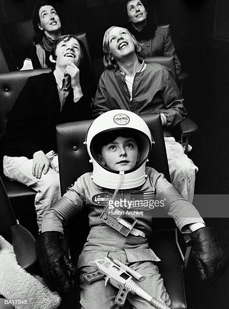 Boy (5-7) wearing astronaut costume and group of people staring up