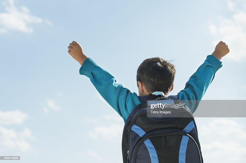 Boy (6-7) wearing backpack punching air : Stock-Foto