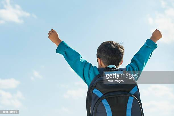 Boy (6-7) wearing backpack punching air