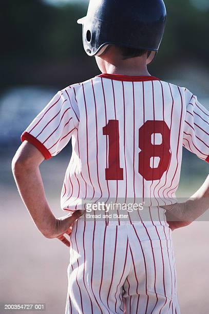 Boy (8-10) wearing baseball uniform with hands on hips, rear view