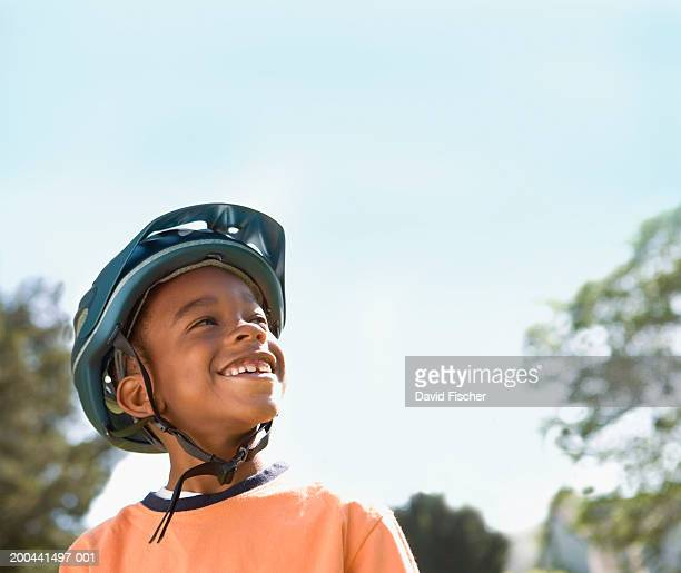 boy (6-8) wearing bicycle helmet, smiling, looking up - cycling helmet stock photos and pictures