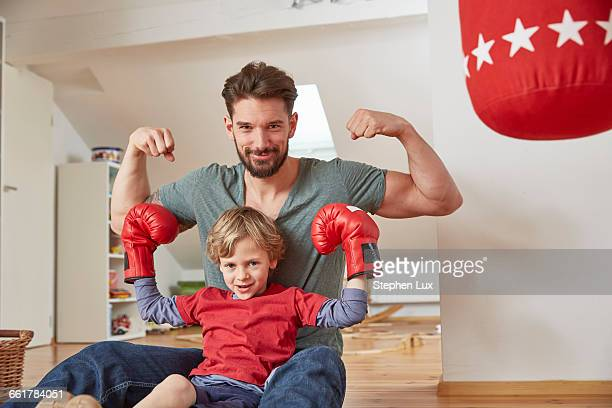 Boy wearing boxing with father, flexing muscles looking at camera