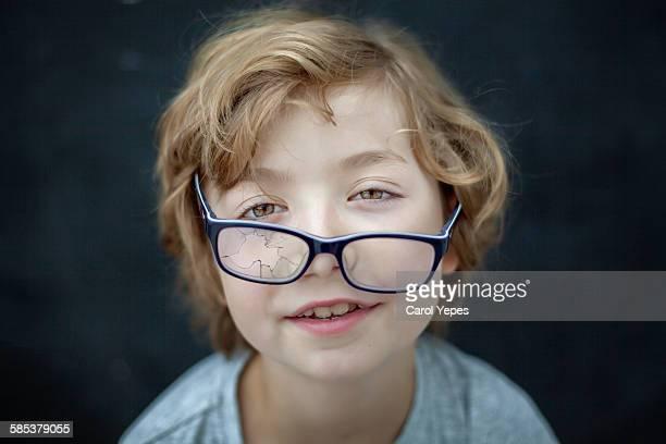 Boy wearing broken glasses