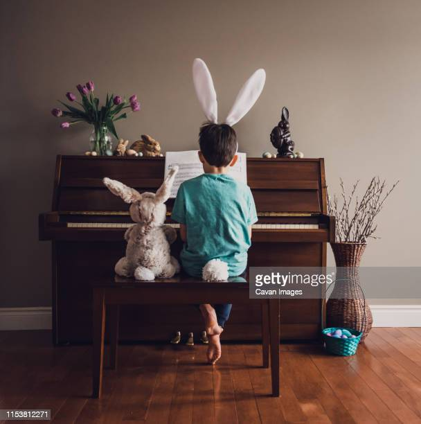 boy wearing bunny ears playing piano with stuffed rabbit beside him. - easter bunny costume stock pictures, royalty-free photos & images