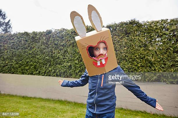 Boy wearing bunny mask in garden