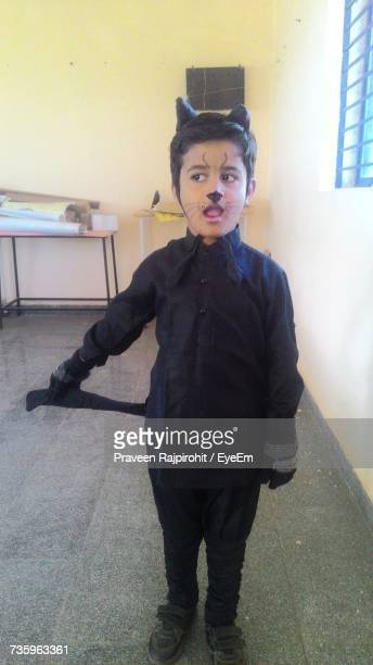 boy wearing cat costume while standing in room - cat costume stock photos and pictures