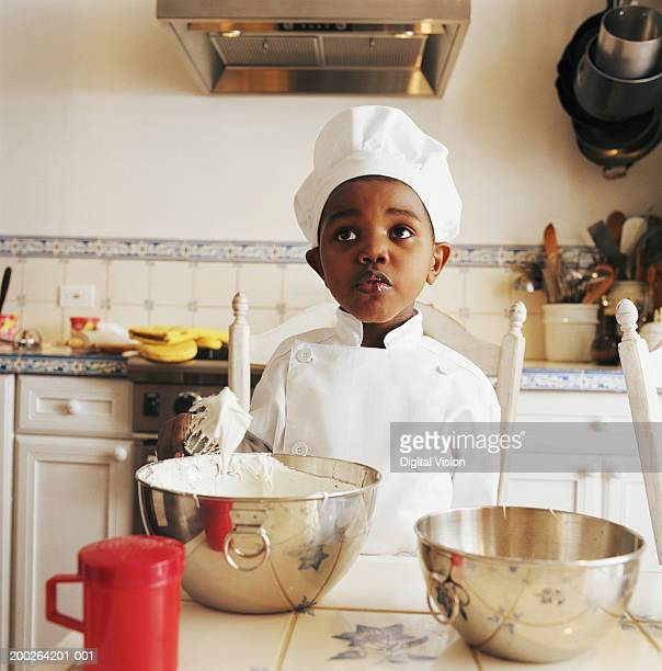 Boy (3-5) wearing chef outfit by bowls in kitchen