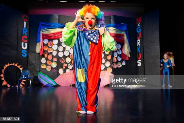 boy wearing clown costume on stage - school play stock photos and pictures