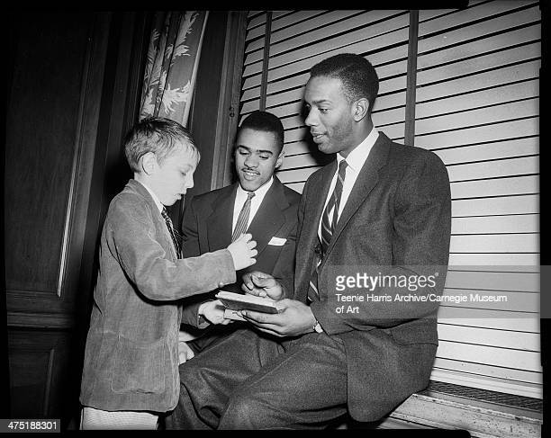 Boy wearing corduroy jacket standing in front of runner Arnold 'Arnie' Sowell and basketball player Sihugo 'Si' Green holding book at Dapper Dan...
