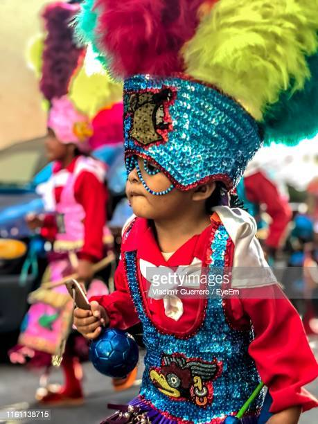 boy wearing costume enjoying at carnival in city - mexican fiesta stock pictures, royalty-free photos & images
