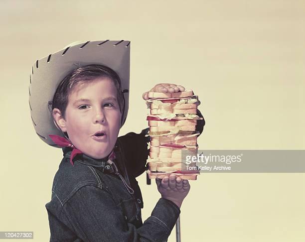 jungen tragen cowboyhut holding big sandwich, porträt - archivmaterial stock-fotos und bilder