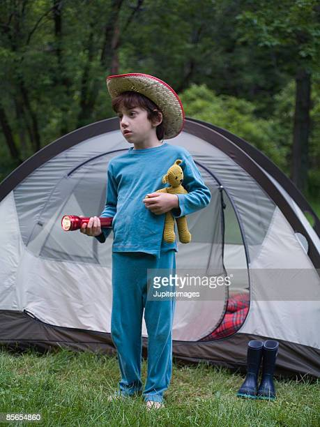 Boy wearing cowboy hat holding flashlight and stuffed bear
