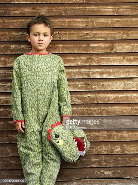 Boy (5-7) wearing crocodile costume, arms by side, portrait