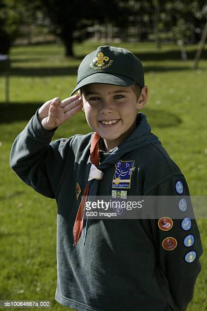 Boy wearing cub scout uniform, saluting, smiling, portrait