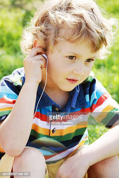 boy (6-7 years) wearing earphones, sitting on grass - 6 7 years stock pictures, royalty-free photos & images