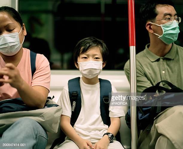 Boy (8-9) wearing face mask on train