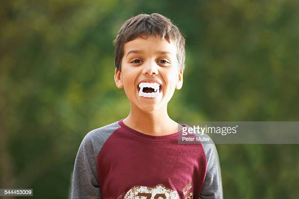 Boy wearing fake vampire teeth with fangs