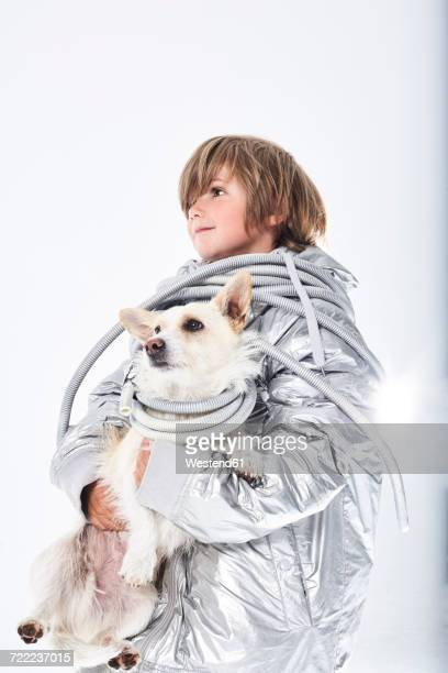 Boy wearing fancy dress carrying dog