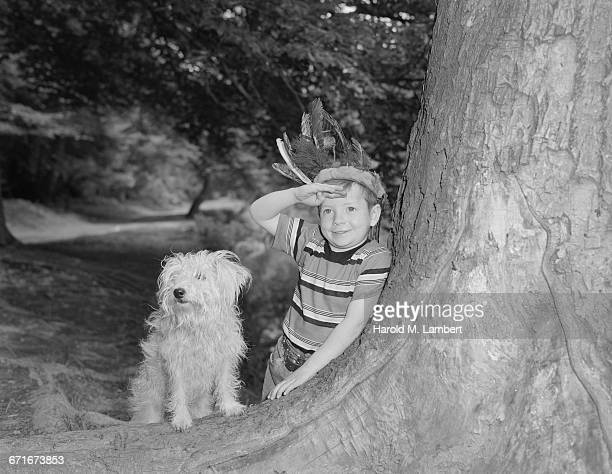 boy wearing feather crown saluting and leaning on tree with his dog - {{relatedsearchurl(carousel.phrase)}} fotografías e imágenes de stock