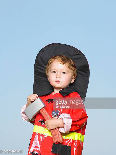 Boy (21-24 months) wearing fire-fighter's costume, portrait