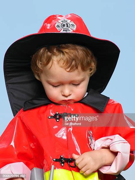 Boy (21-24 months) wearing fire-fighter's costume, portrait