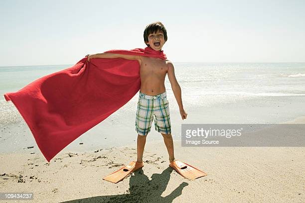 Boy wearing flippers and red cape on beach