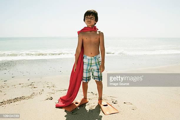 Junge mit Schwimmflossen und red cape am Strand