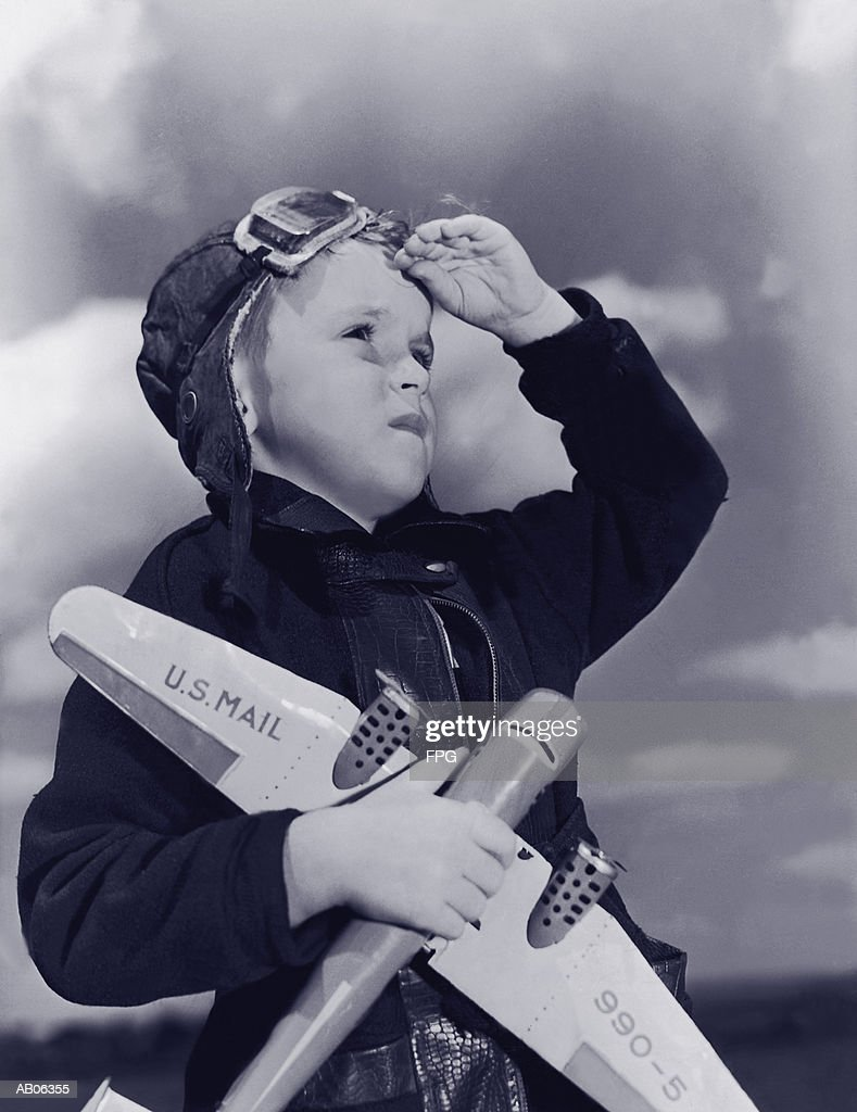 Boy (8-10) wearing flying cap and goggles holding toy plane (B&W) : Foto de stock