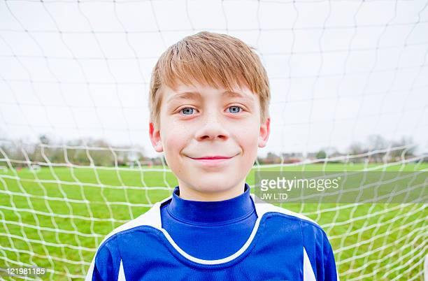 Boy wearing football shirt in goal, portrait
