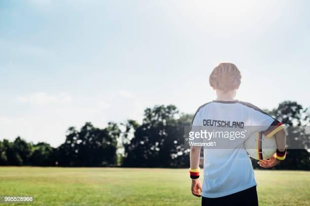 boy wearing football shirt with germany written on back - trikot stock-fotos und bilder