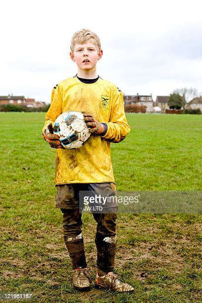 boy wearing football strip holding football, portrait - portiere posizione sportiva foto e immagini stock