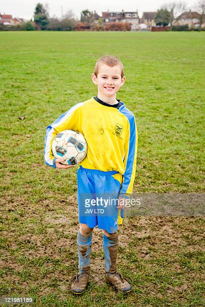 boy wearing football strip holding football, portrait - football strip stock pictures, royalty-free photos & images