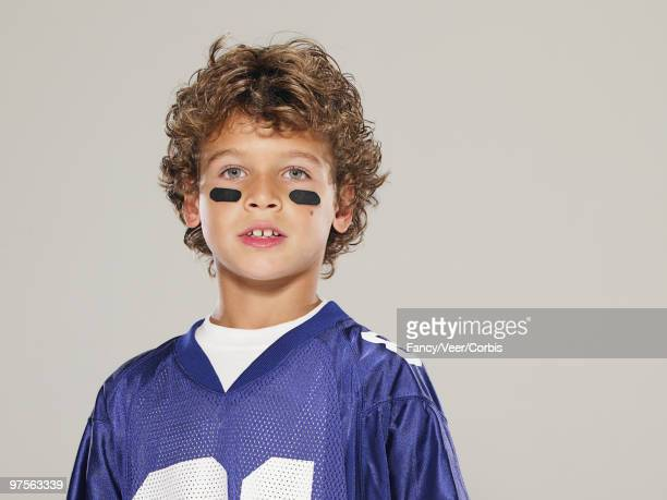 boy wearing football uniform - eye black stock photos and pictures
