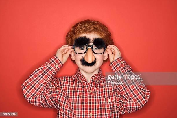 Boy wearing funny disguise in studio