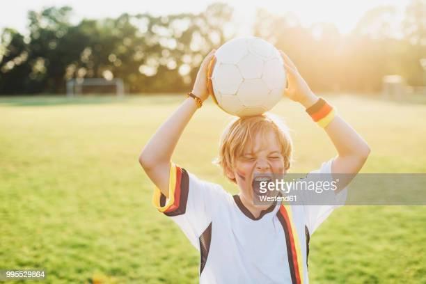 boy wearing german soccer shirt screaming for joy - meisterschaft stock-fotos und bilder