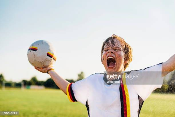 boy wearing german soccer shirt screaming for joy, standing in water splashes - camiseta deportiva fotografías e imágenes de stock