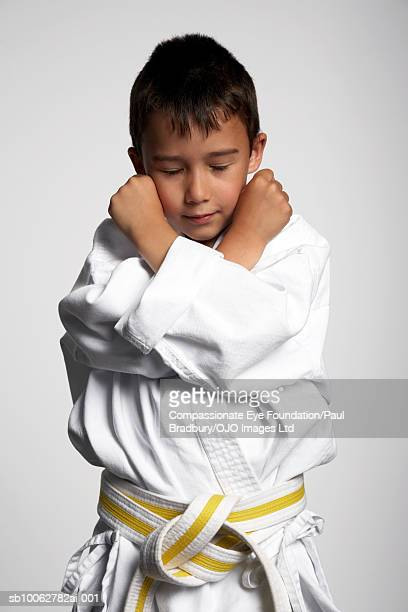 Boy (6-7) wearing gi, standing with arms crossed and eyes closed