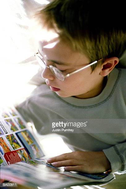 Boy (6-8) wearing glasses reading comic, close-up
