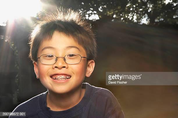 Boy (7-9) wearing glasses, smiling, portrait