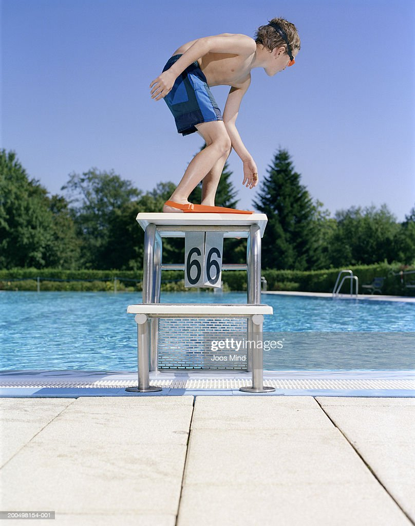 Boy Wearing Goggles And Flippers On Starting Block At ...